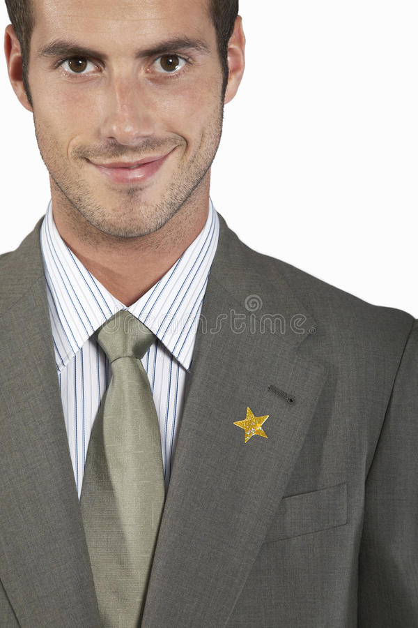 Businessman With Gold Star On Suit. Closeup portrait of a young businessman with gold star on suit royalty free stock photos