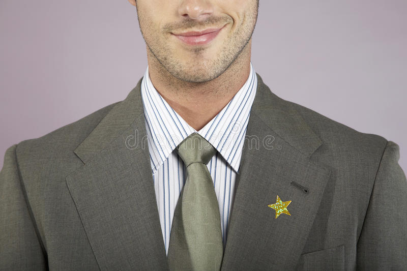Businessman With Gold Star On Suit. Closeup of a smiling young businessman with gold star on suit stock image