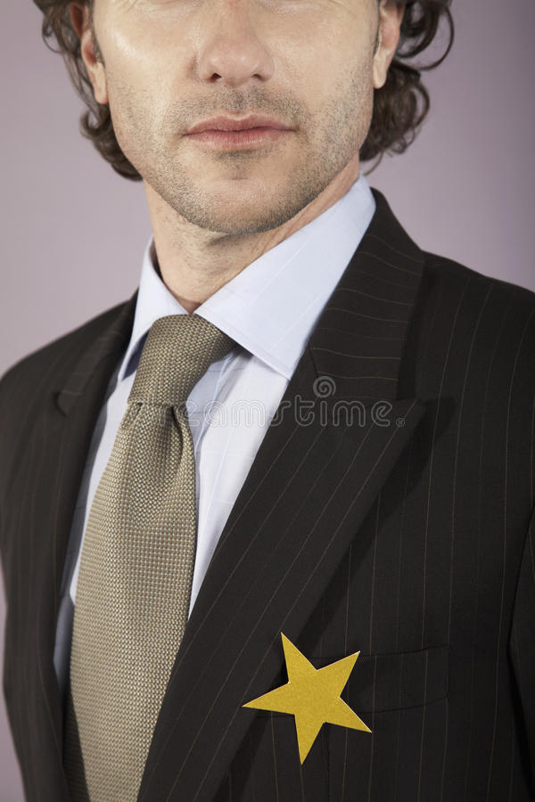 Businessman With Gold Star On Suit. Closeup of a young businessman with gold star on suit royalty free stock image