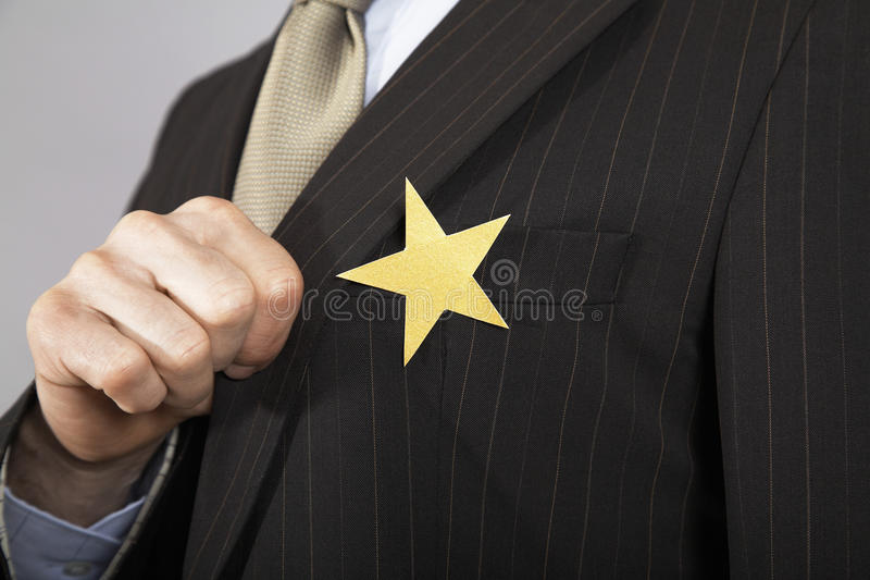 Businessman With Gold Star On Suit. Extreme closeup of a businessman with gold star on suit stock photography