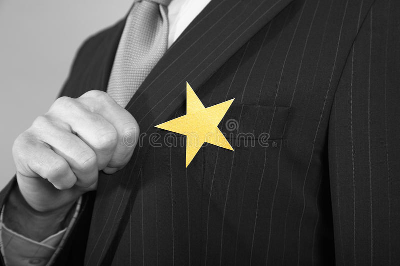 Businessman With Gold Star On Suit. Extreme closeup of a businessman with gold star on suit stock image