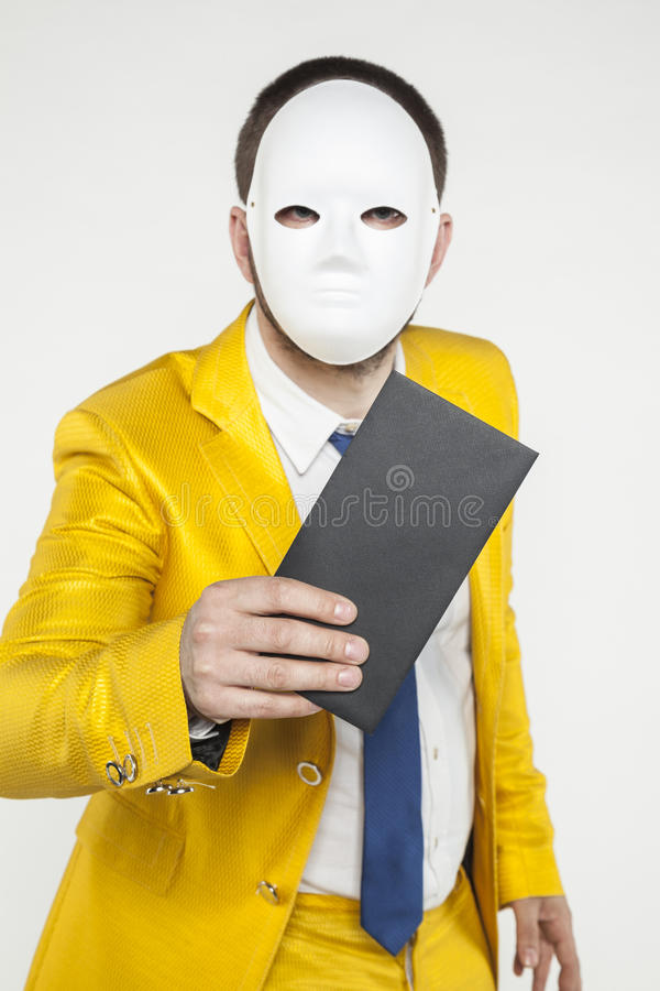 Businessman in a gold suit, holding an envelope in his hand. On the withe background royalty free stock photo
