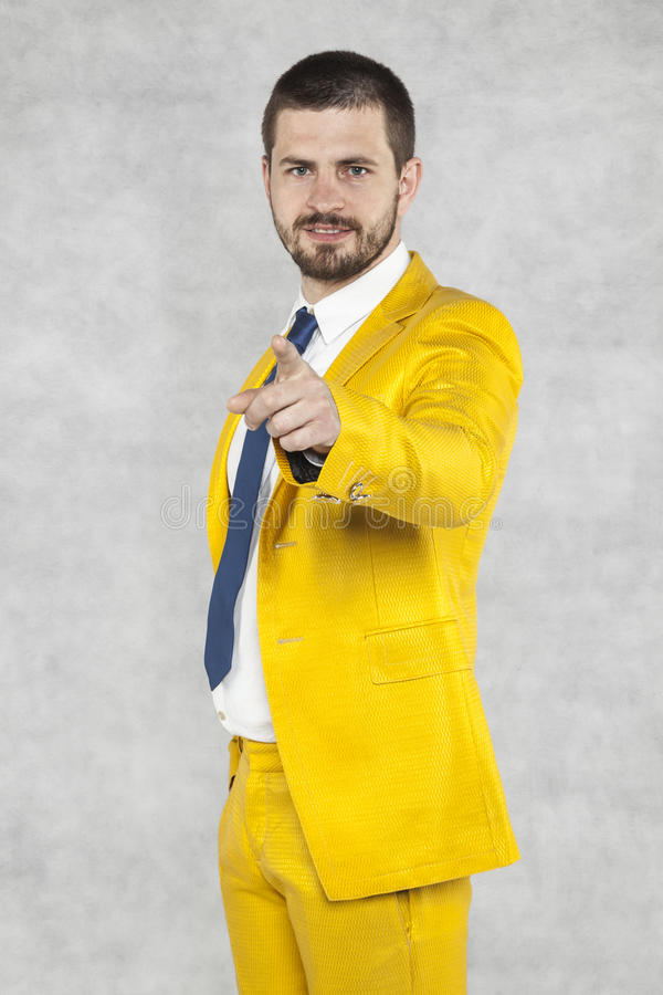 Businessman in a gold suit pointing at you. Business man in a gold suit pointing at you stock photography