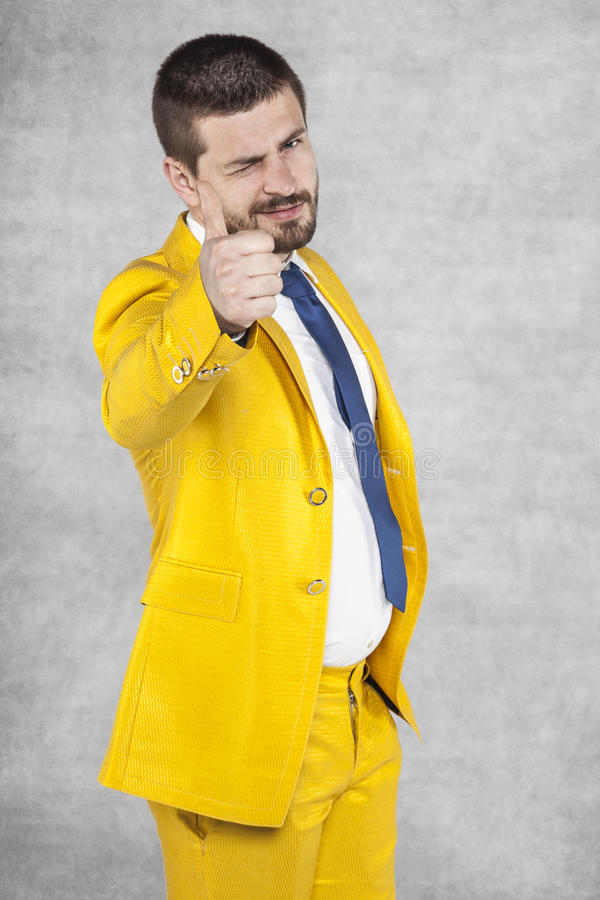 Businessman in gold suit show thumbs up. Business man in gold suit show thumbs up stock images