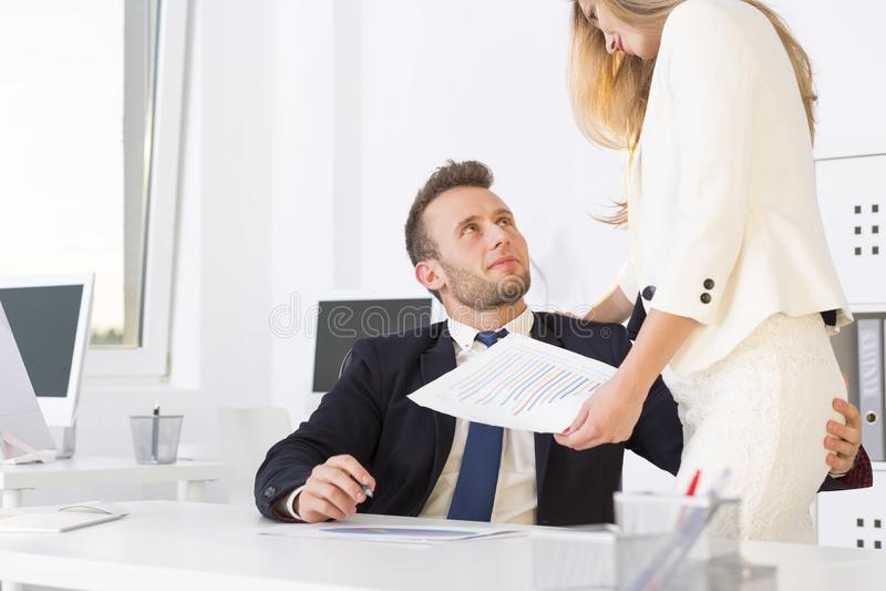 Businessman grabbing womans buttocks stock photo