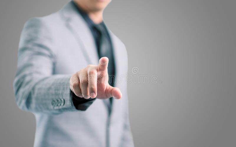 Businessman in gray suit is pointing his finger to touch the screen concept. With gray background stock photos