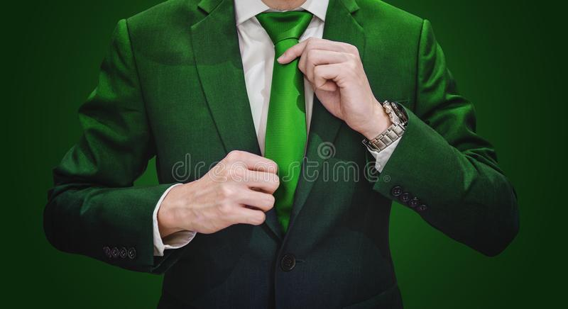 Businessman in green suit tying green necktie. Environment, agriculture and green business. Businessman in green suit tying green necktie. Environmental royalty free stock photography