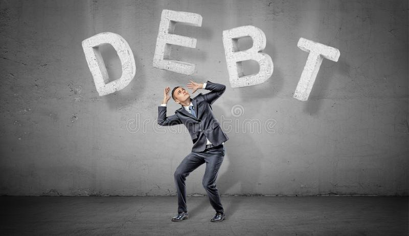 A businessman on a grey background cowers under large concrete letters making a word DEBT above him. Business and finance. Credit and loss. Mortgage conditions stock photos