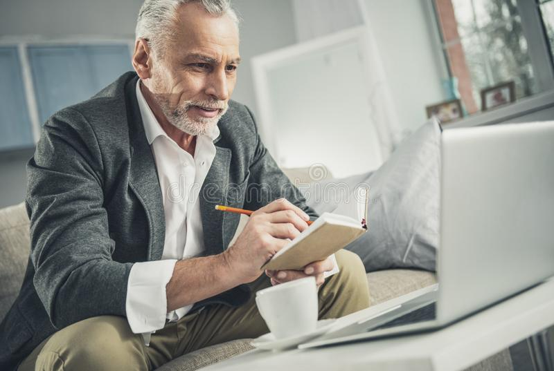 Businessman in grey suit holding notebook in his hands stock image
