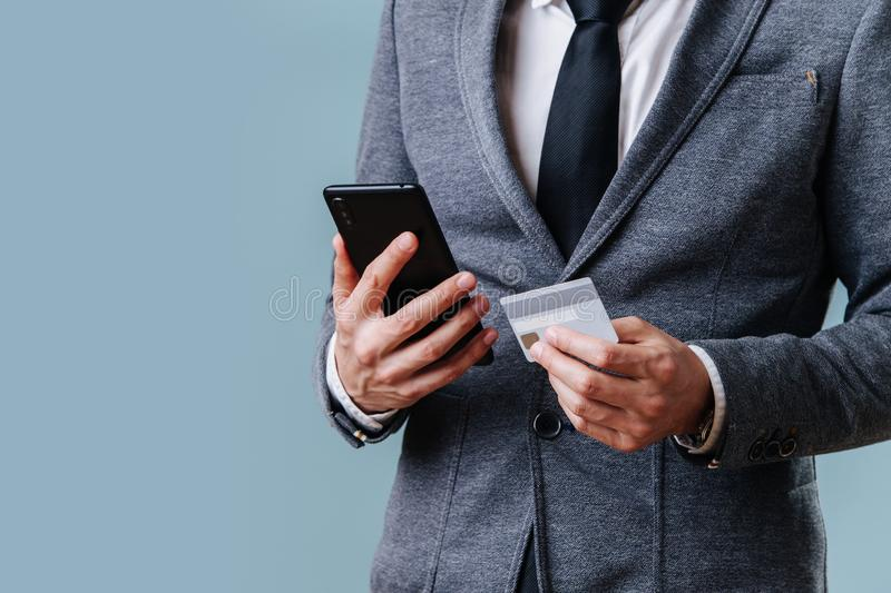 Businessman in a suit making money transaction on his phone over blue background royalty free stock images