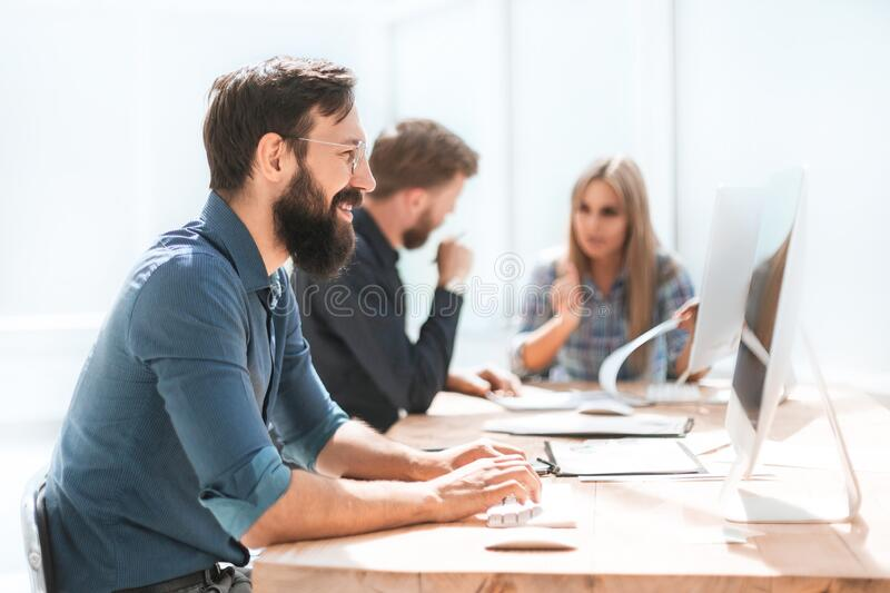 Businessman and a group of employees working in the office. stock photo