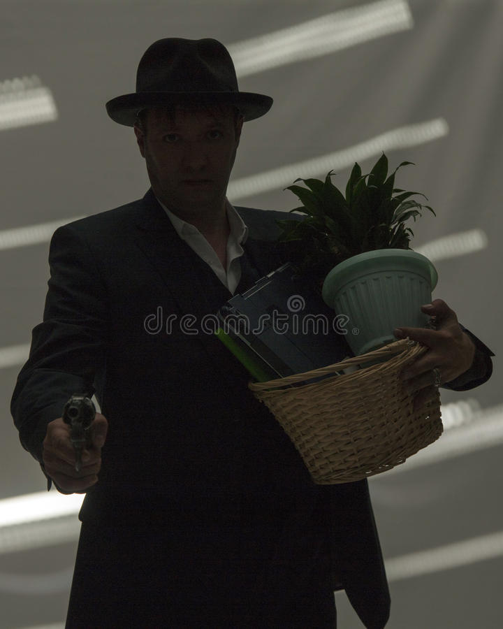 Businessman with gun hold personal belongings. Businessman in suit and hat with gun hold basket with personal belongings in dark room royalty free stock photos