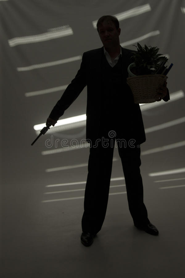 Businessman with gun hold personal belongings. Businessman in suit and hat with gun hold basket with personal belongings in dark room royalty free stock photo