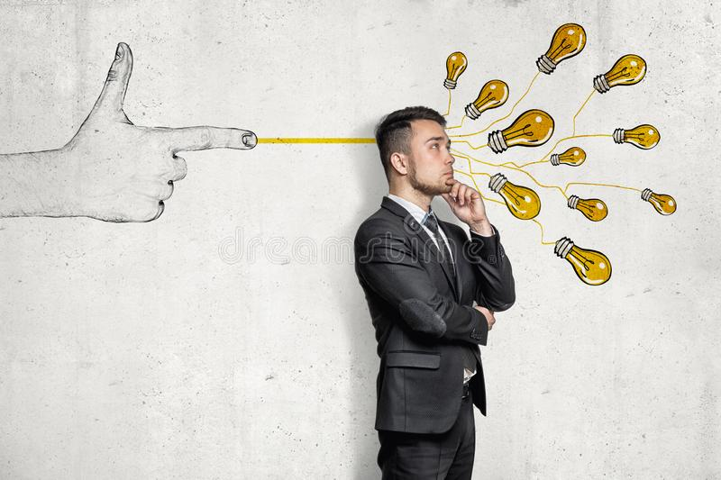 Businessman in half-turn, hand on chin, standing near wall with hand-drawn finger gun shooting bunch of yellow electirc royalty free stock photography