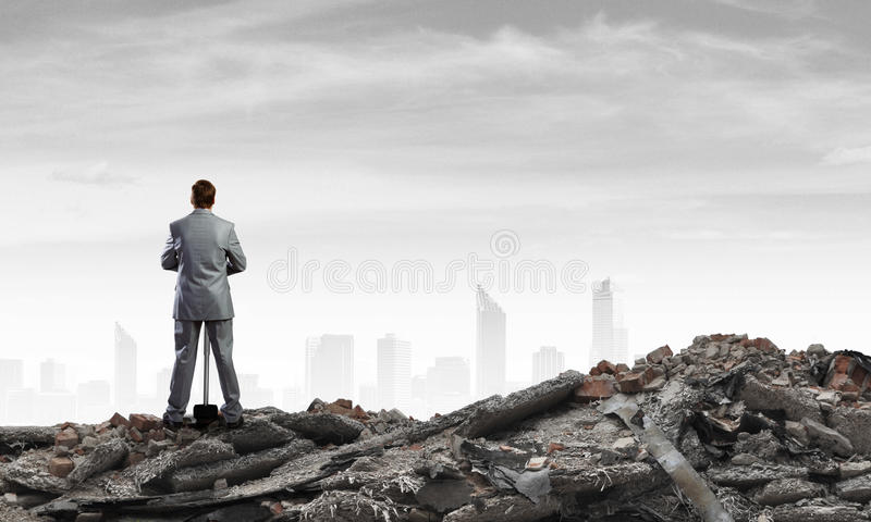 Businessman with hammer. Young determined businessman with big hammer in hands standing on ruins royalty free stock photo