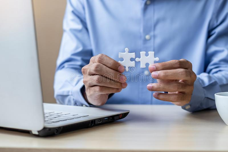 Businessman Hand connecting couple puzzle piece in office. Business solutions, mission, successful, goals and strategy concepts. Businessman Hand connecting royalty free stock photo
