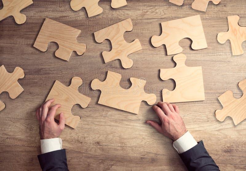Businessman hand connecting jigsaw puzzle stock photos