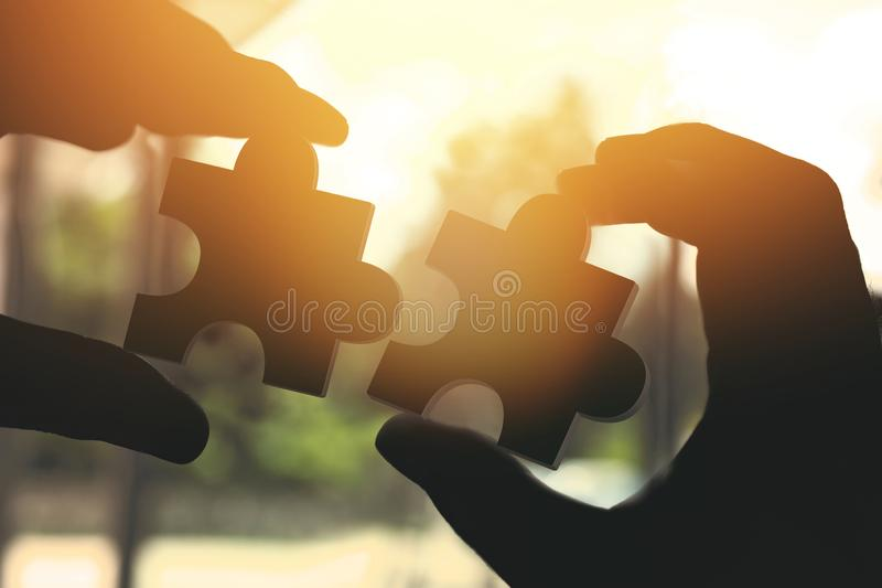 Businessman hand connecting jigsaw puzzle with sunlight effect. royalty free stock image