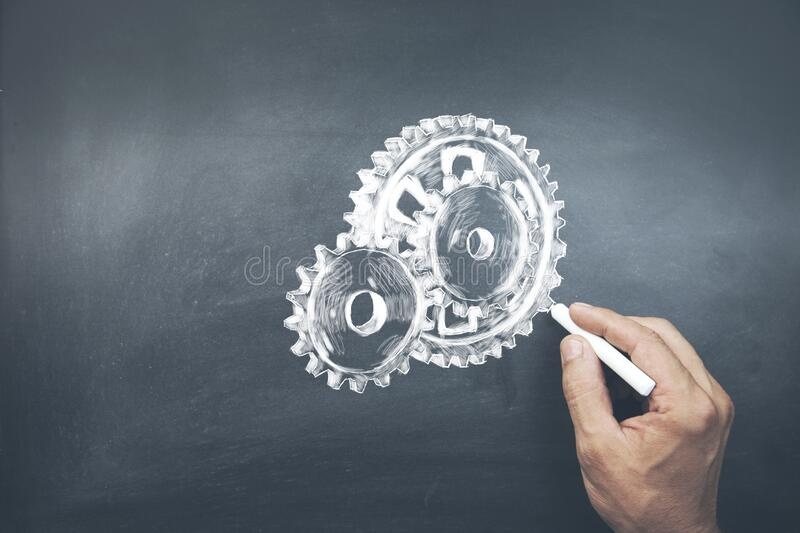 Businessman hand drawing with chalk gears mechanism as teamwork concept.  royalty free stock photo