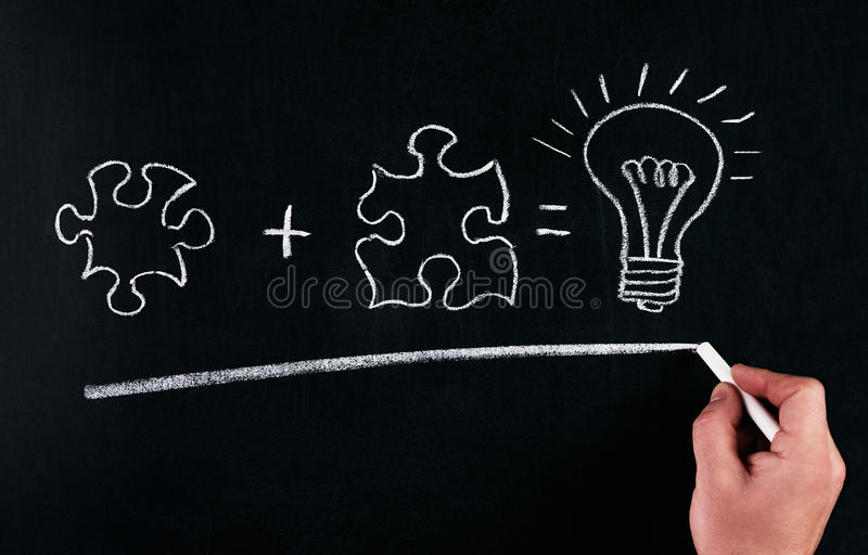 Businessman Hand drawing puzzle on blackboard to explain business concept. Solving puzzle together. Drawing light bulb on blackbo royalty free stock photography