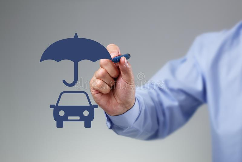 Car insurance. Businessman hand drawing an umbrella above a family car concept for car insurance, protection, security and finance stock image