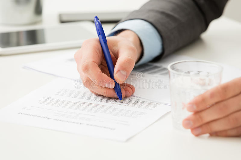 Businessman hand filling in business document stock photos