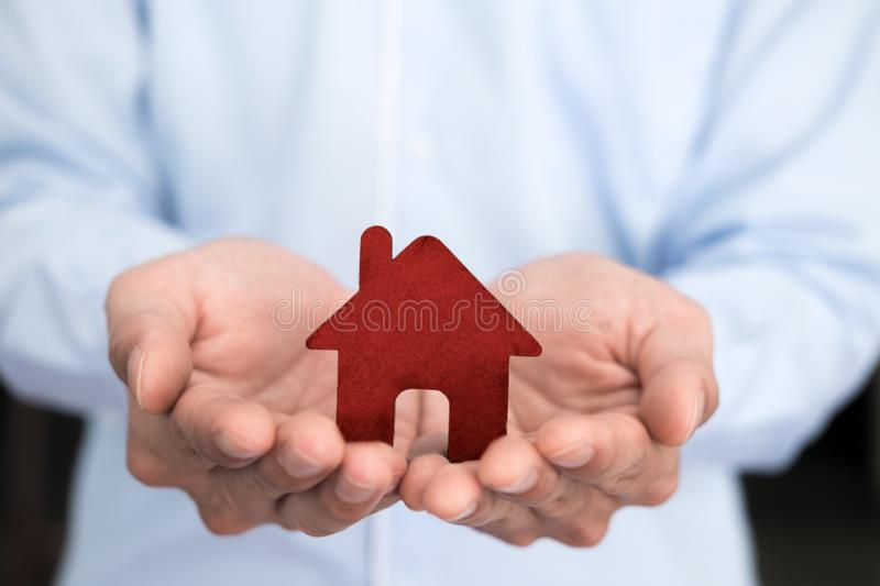 Businessman hand hold the house model saving small house. Business man hand hold the house model saving small house. House insurance stock images