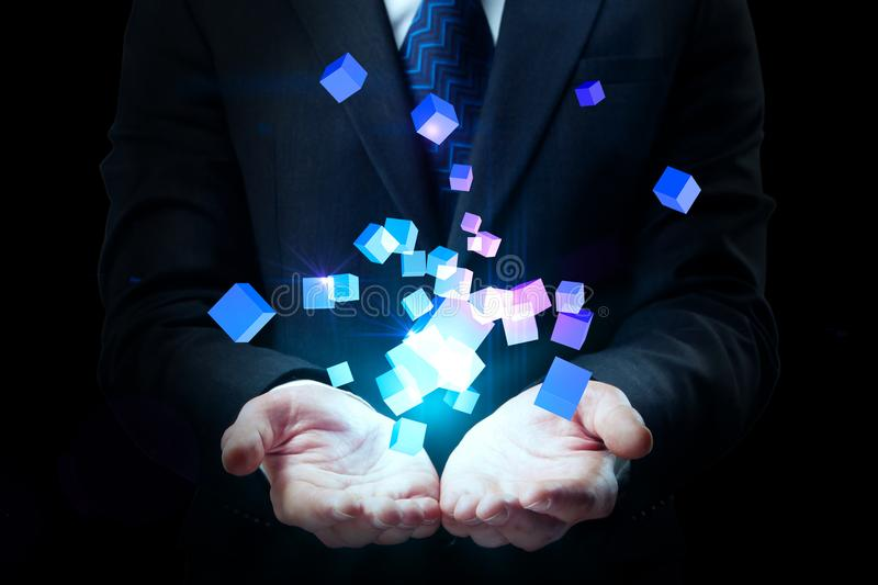 Future and creation concept. Businessman hand holding abstract glowing cubes on black background. Future and creation concept royalty free stock photos
