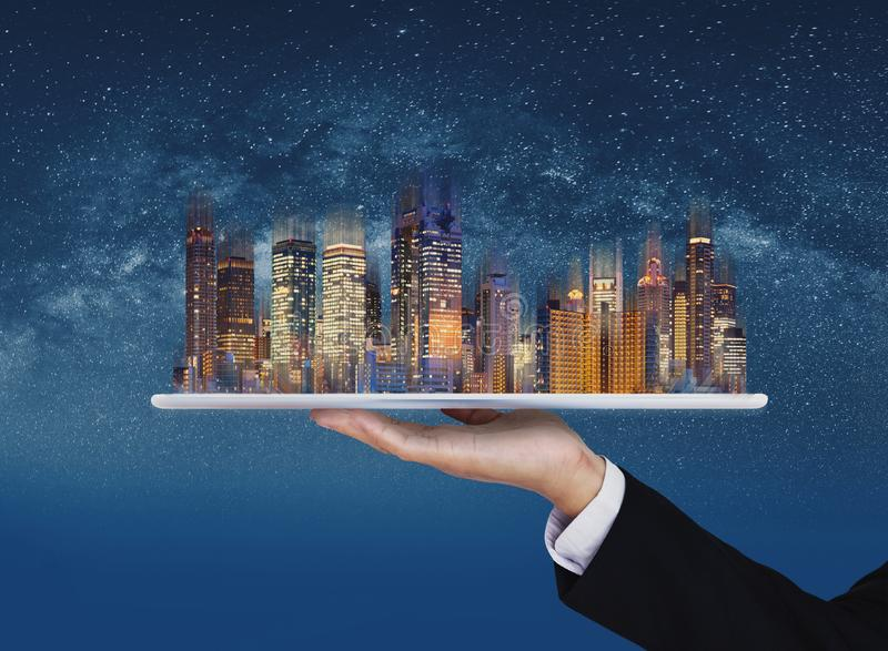 Businessman hand holding digital tablet with modern buildings hologram. Smart city, building technology and real estate business. Businessman hand holding stock photos