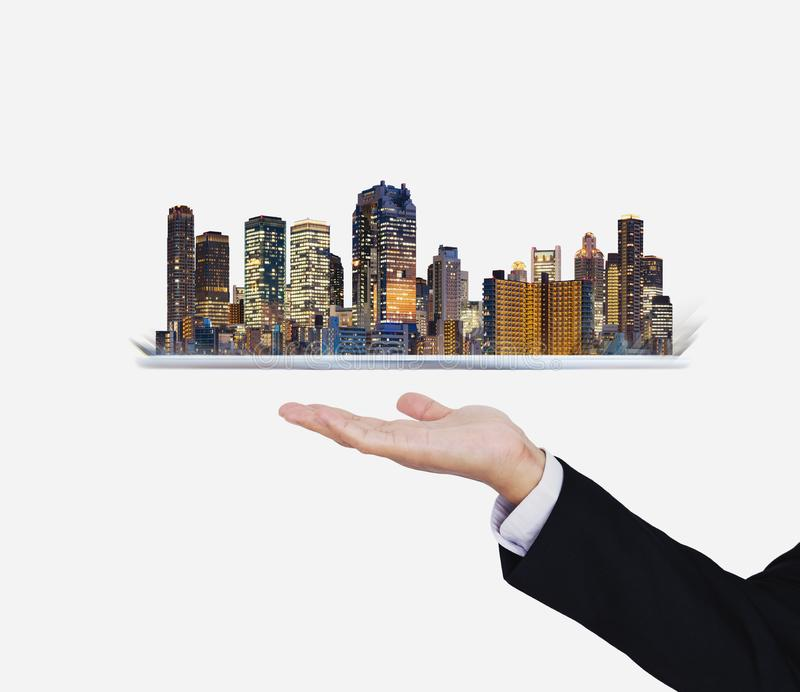 Businessman hand holding digital tablet with modern buildings hologram. Smart city, building technology and real estate business royalty free stock photography