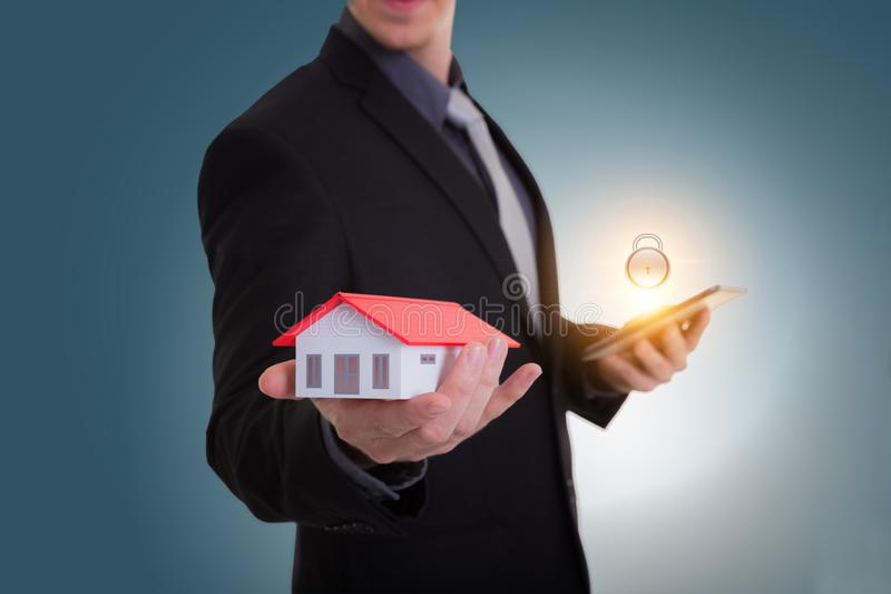 Businessman hand holding house representing home ownership and t royalty free stock image