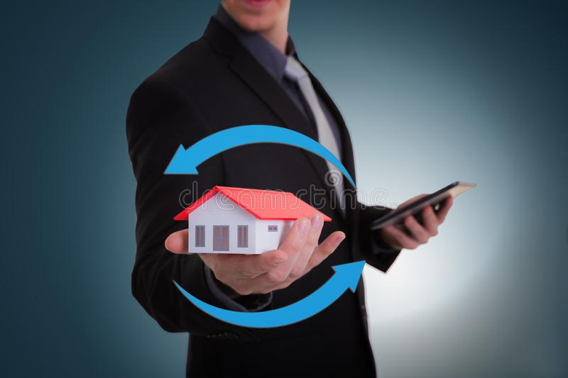 Businessman hand holding house representing home ownership and t stock photos