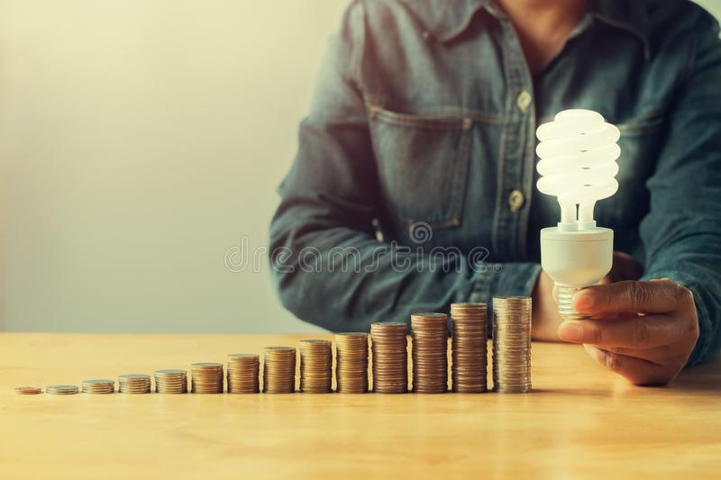 businessman hand holding led light and money stack on table in o royalty free stock photography