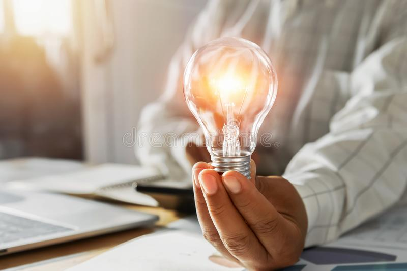 Businessman hand holding light bulb in office. concept save energy power. Accounting, money, electricity, finance, lightbulb, saving, knowledge, financial stock photo