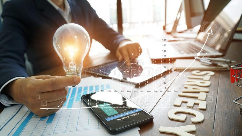 Businessman hand holding lightbulb with business documents and strategy word on office table and banking data on smart phone stock photos