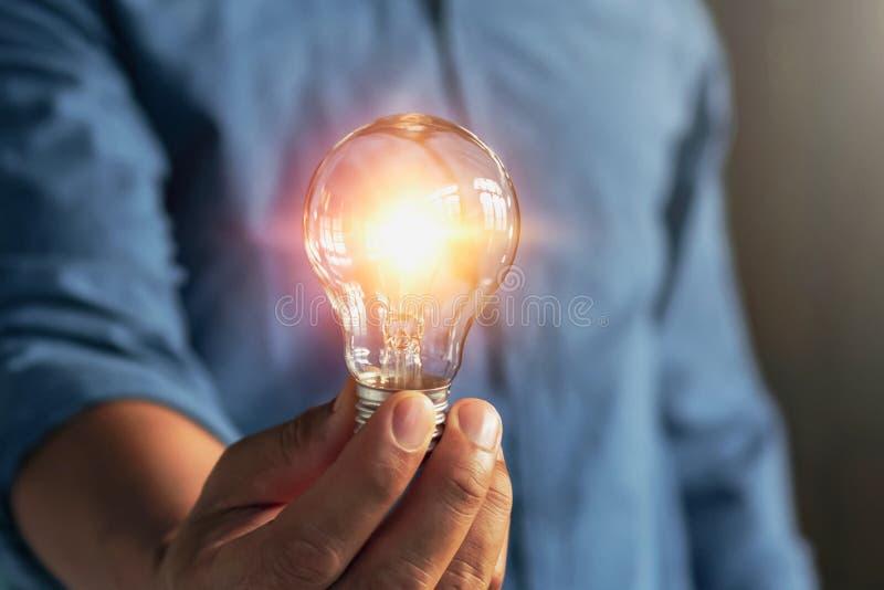 Businessman hand holding lightbulb. idea Alternative energy concept saving electricity. New, led, finger, showing, hot, modern, black, object, think royalty free stock image