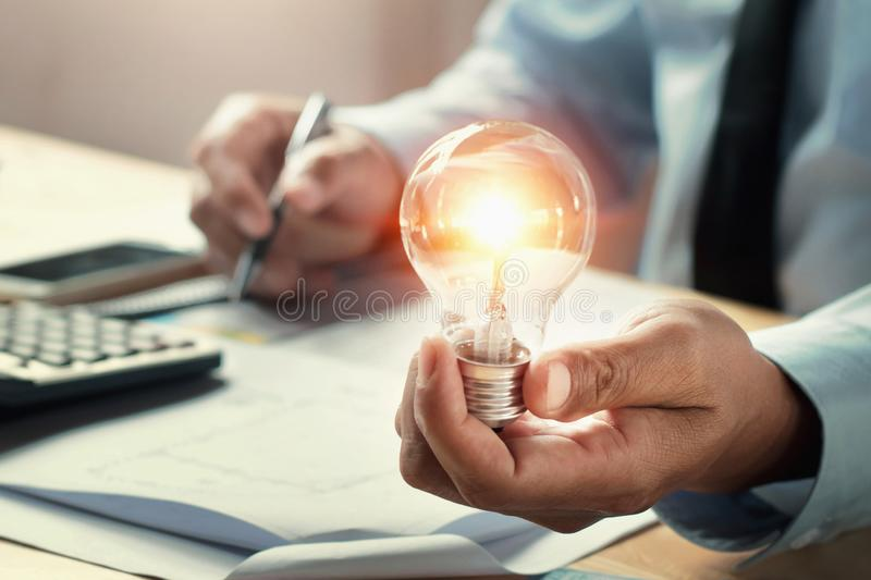 businessman hand holding lightbulb in office. concept idea saving royalty free stock photography