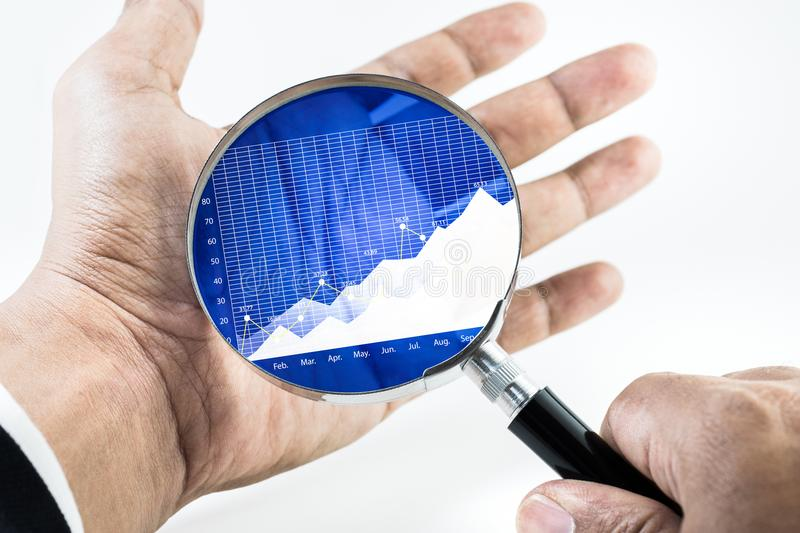 Businessman hand holding magnifying with growing graph chart. On palm.For business growth and financial success concept ideas royalty free stock images