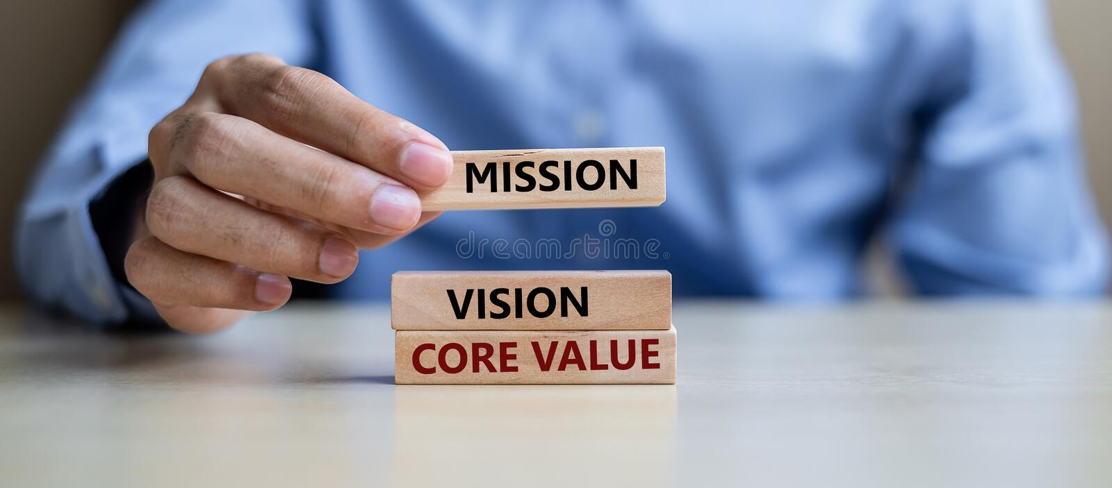 Businessman hand holding wooden building blocks with MISSION, VISION, CORE VALUE Concepts stock images
