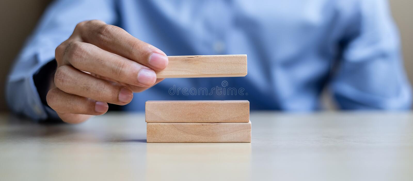 Businessman hand holding wooden building blocks on table background. Business planning, Risk Management, Solution and strategy royalty free stock images
