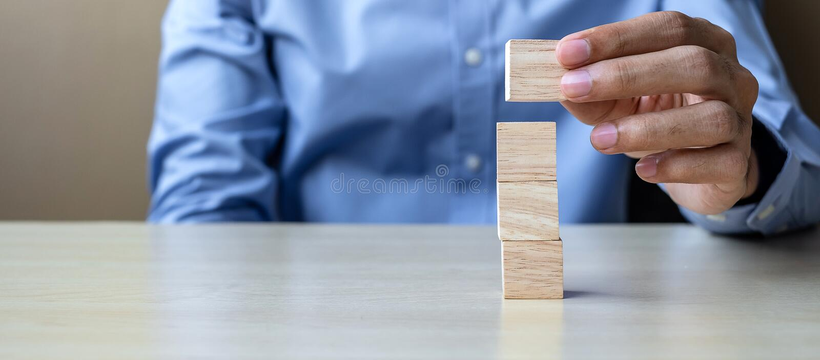 Businessman hand holding wooden cube with GOAL text on table background. success, strategy, solution and business concepts. Businessman hand holding wooden cube royalty free stock photography