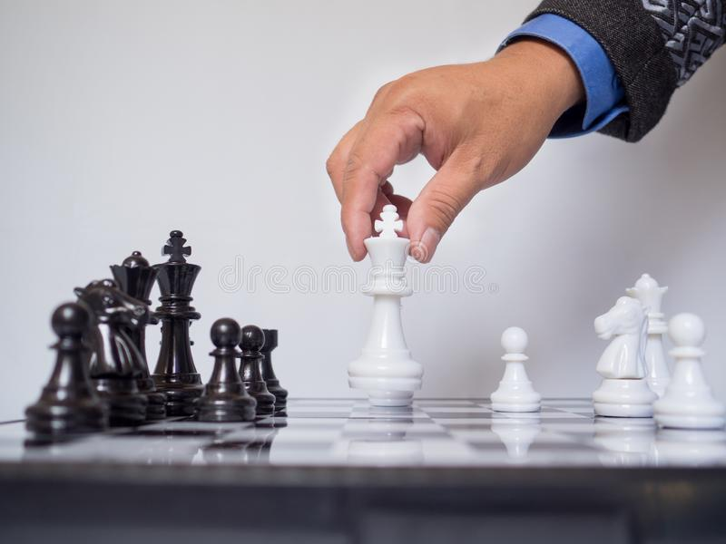 Businessman hand moving king chess piece on board with white background, challenges planning business strategy to success concept stock image