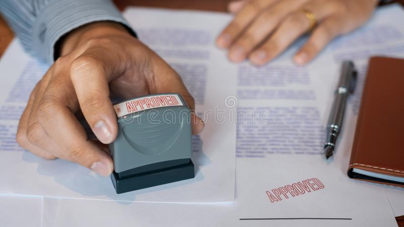 Businessman Hand notary public hand ink appoval stamper Stamping seal On Approved Contract Form documents contract, loan money stock image