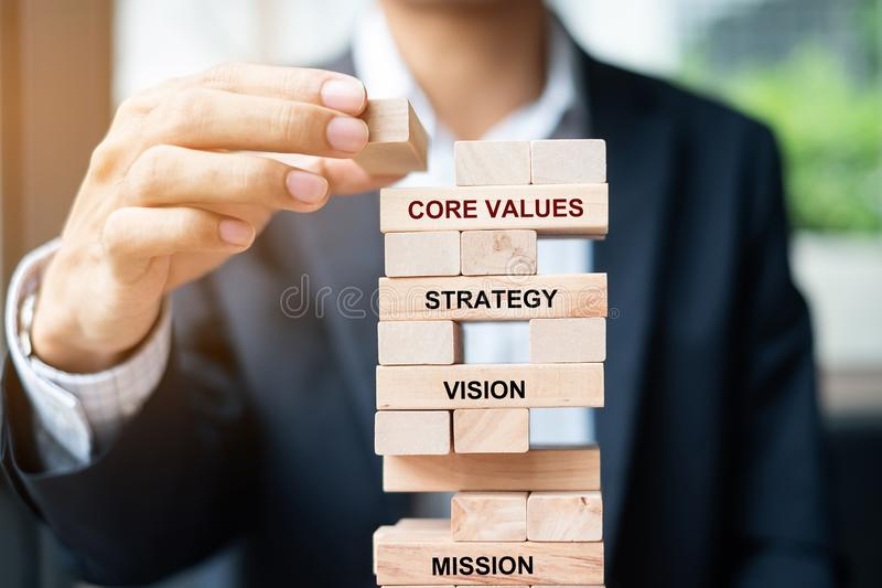 Businessman hand placing or pulling wooden block on the tower. Business planning, Risk Management, Solution, Mission, Vision, Core. Values  and strategy royalty free stock photo