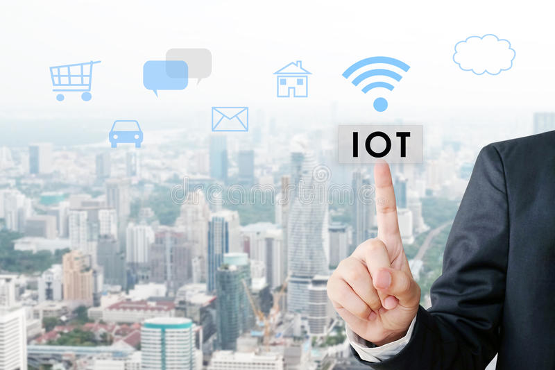 Businessman hand pointing the internet of things button over icons and blur city scrape background stock image