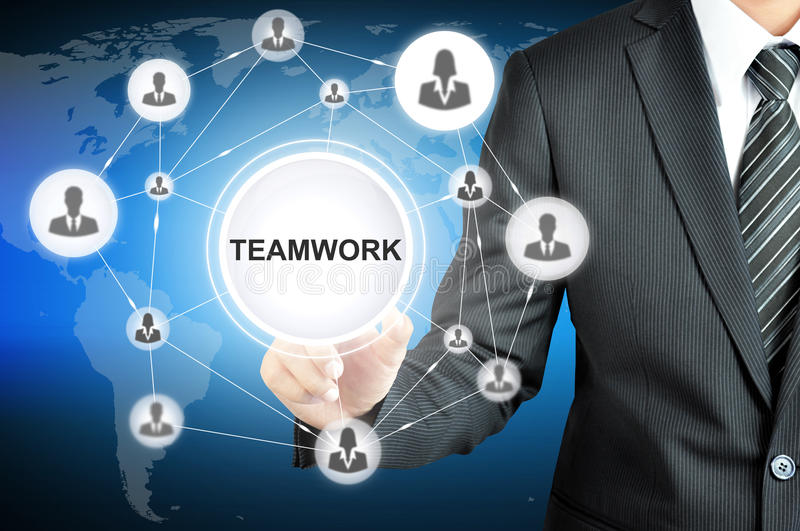 Businessman hand pointing on TEAMWORK sign on virtual screen royalty free stock photo