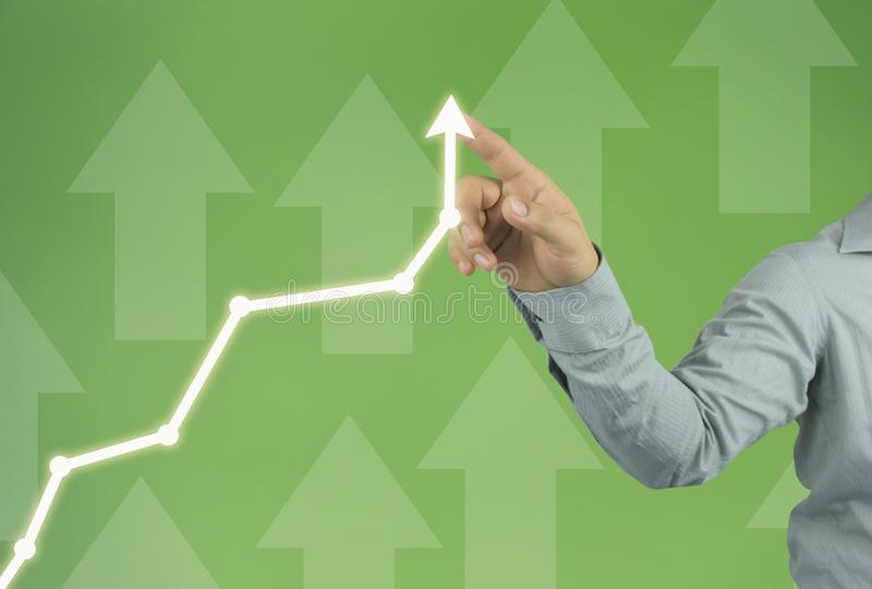 Businessman hand pointing to the top line of a arrow on green ba. Ckground and have copy space for design in your work stock photos