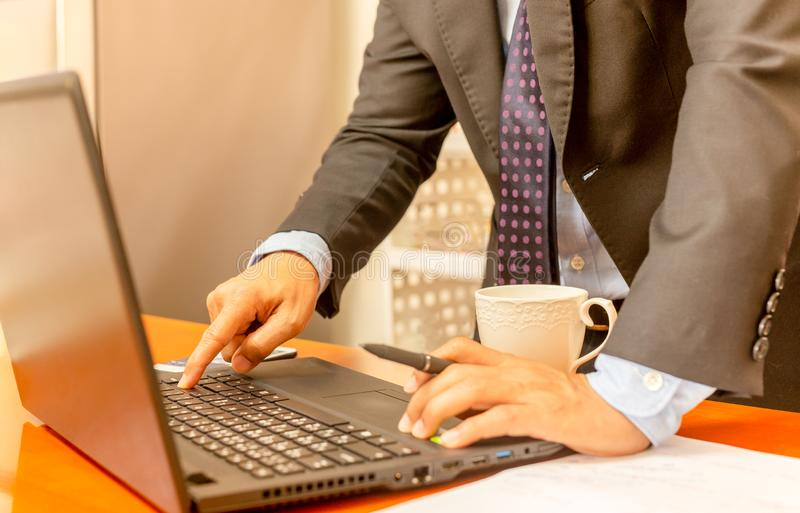 Businessman hand press enter laptop keyboard with cup of coffee on the table. stock image