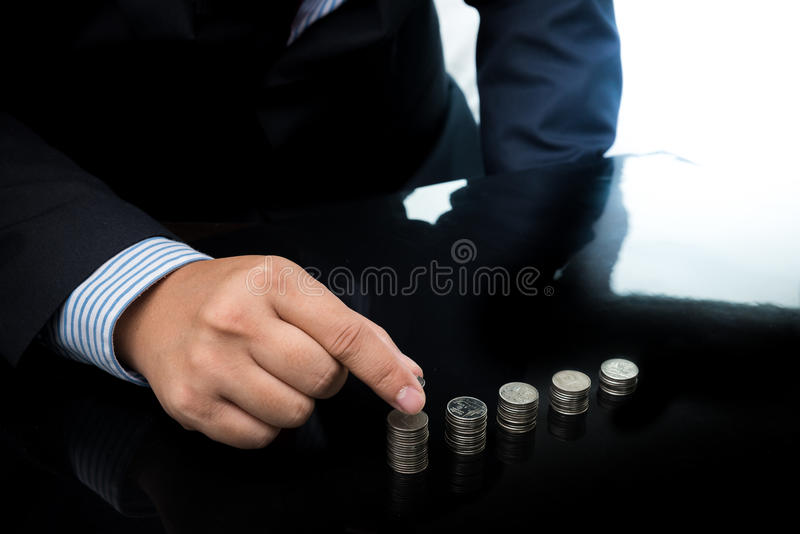 Businessman Hand Put Coins To Stack Of Coins. Closeup Of Businessman Hand Put Coins To Stack Of Coins stock images