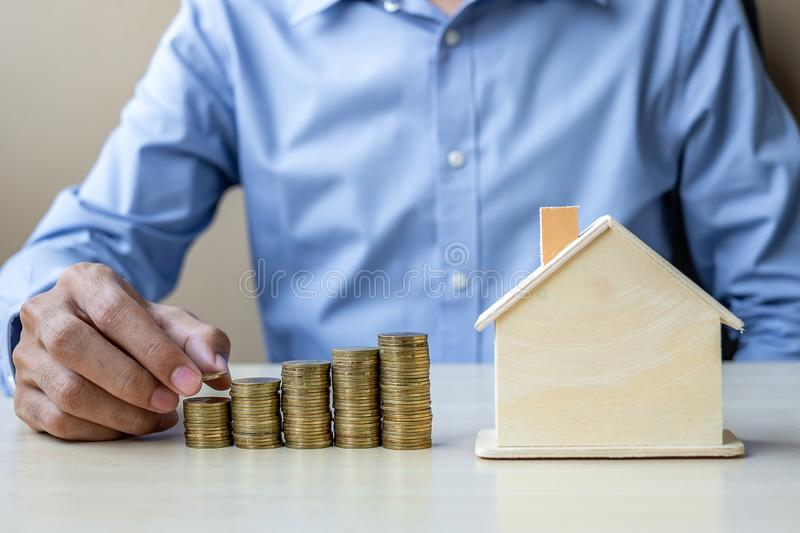 Businessman hand putting golden coin on growing money stairs or stack with house model. business, investment, retirement planning royalty free stock images